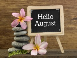 stack of pebbles and mini blackboard with text  hello august